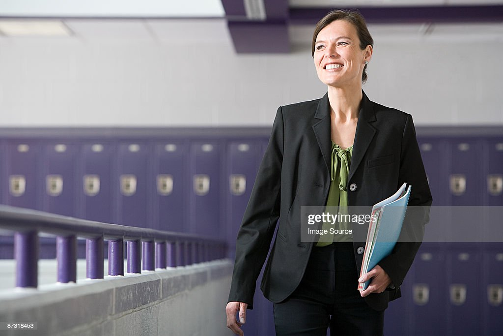 A teacher walking down a corridor : Stock Photo