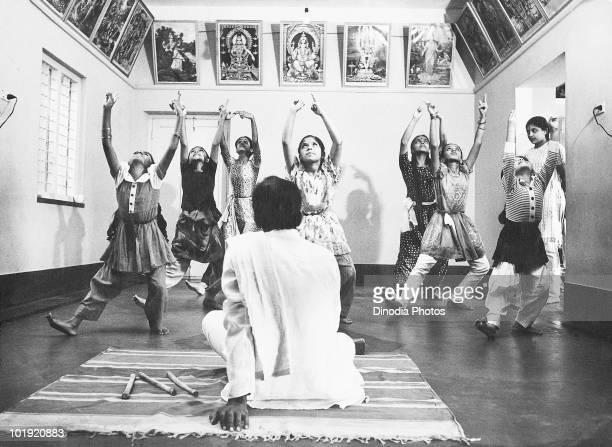 A teacher watches his students practising the classical Indian Bharatanatyam dance Bangalore Karnataka India 1976
