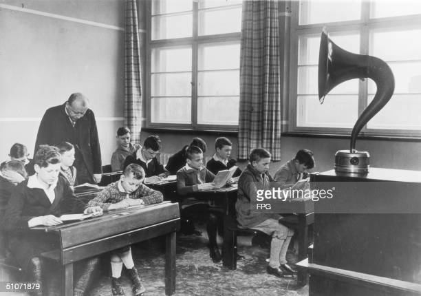 A teacher watches over a class of industrious schoolboys circa 1925