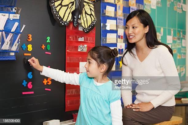 Teacher watching student doing math at blackboard