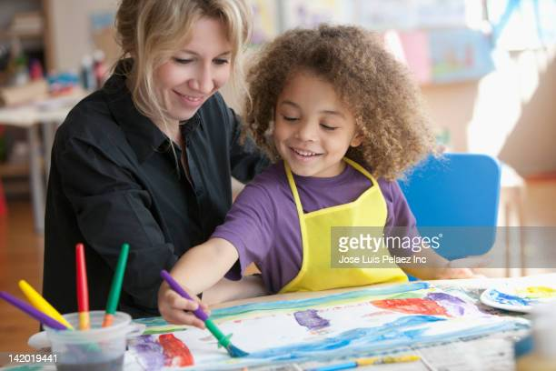 Teacher watching student painting picture