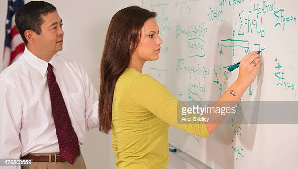 Teacher watching student writing on whiteboard