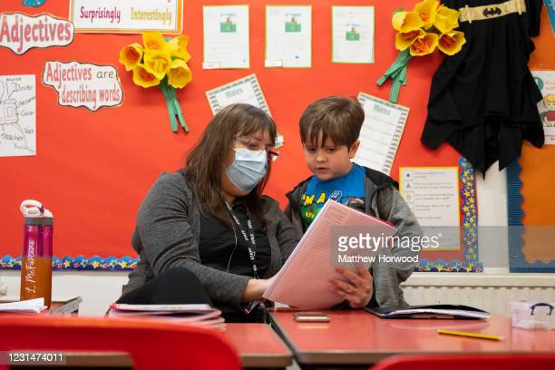 Teacher wearing a face mask helps a child during a lesson at Bryn Hafod Primary School on March 2, 2021 in Cardiff, Wales. Children aged three to...