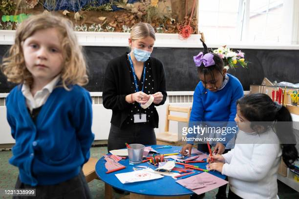 Teacher wearing a face mask helps children at Roath Park Primary School on February 23, 2021 in Cardiff, Wales. Children aged three to seven began a...