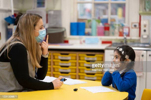 Teacher wearing a face mask teaches a child at Roath Park Primary School on February 23, 2021 in Cardiff, Wales. Children aged three to seven began a...