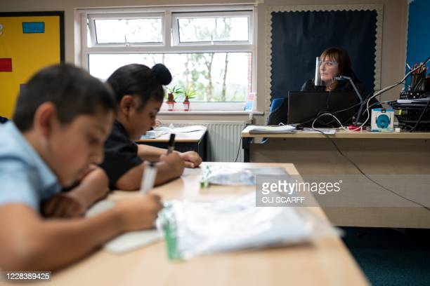 Teacher, wearing a face visor due to the COVID-19 pandemic, teaches year five pupils, with their own individual stationery and books in plastic...