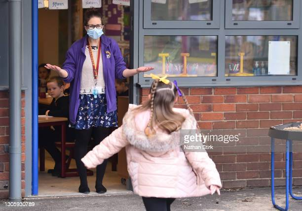 Teacher wearing a mask welcomes a child back to class at St Mary's CE Primary School on March 08, 2021 in Stoke on Trent, England. England's schools...