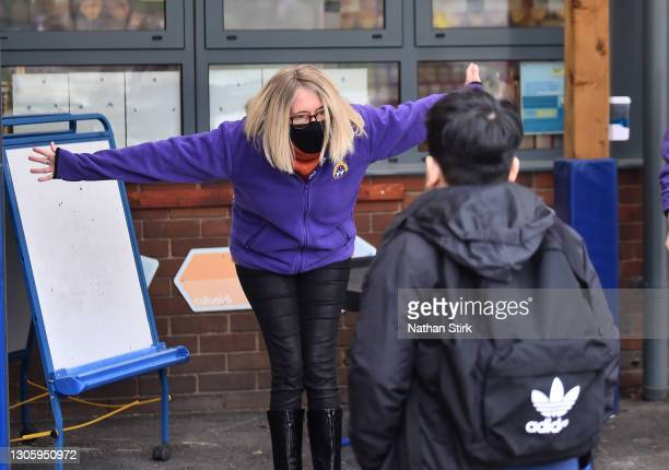 Teacher wearing a mask welcomes a student back to school at St Mary's CE Primary School on March 08, 2021 in Stoke on Trent, England. England's...