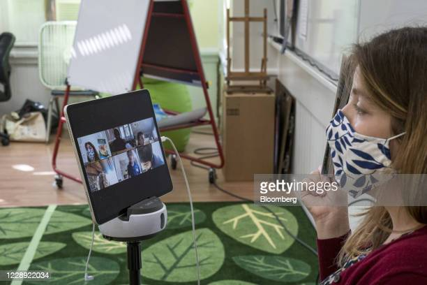 Teacher wearing a protective mask speaks to students learning remotely using a Zoom Video Communications Inc. Application at an elementary school in...