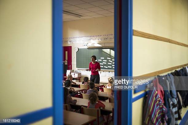 A teacher welcomes pupils in a classroom at the elementary school on September 4 2012 in Paris after the start of the new school year AFP PHOTO /...