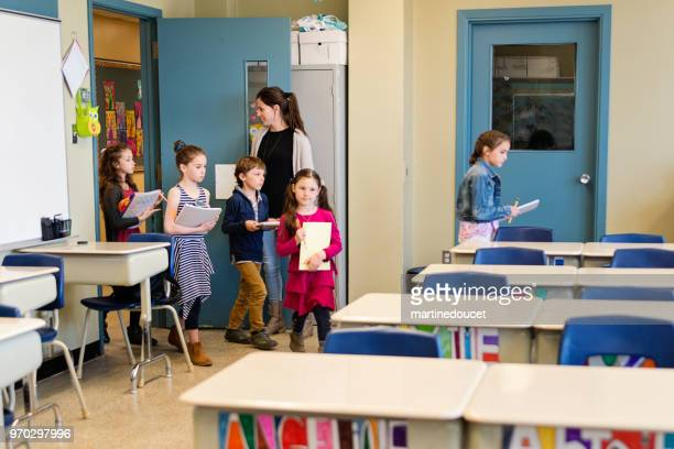 Teacher welcoming students in elementary classroom.