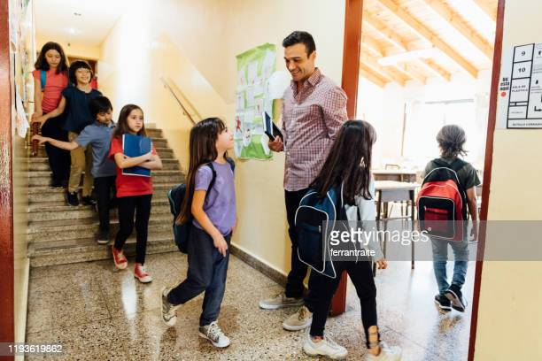 teacher welcoming students to class - showing respect stock pictures, royalty-free photos & images