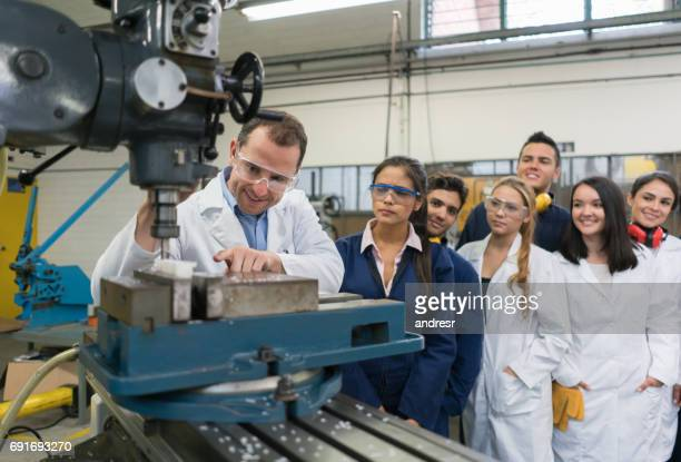 teacher with a group of students in an engineering class - mechatronics stock pictures, royalty-free photos & images