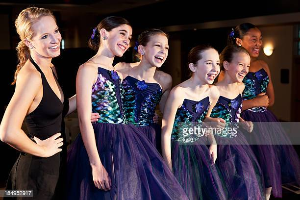 Teacher with ballet dancers in costume on stage