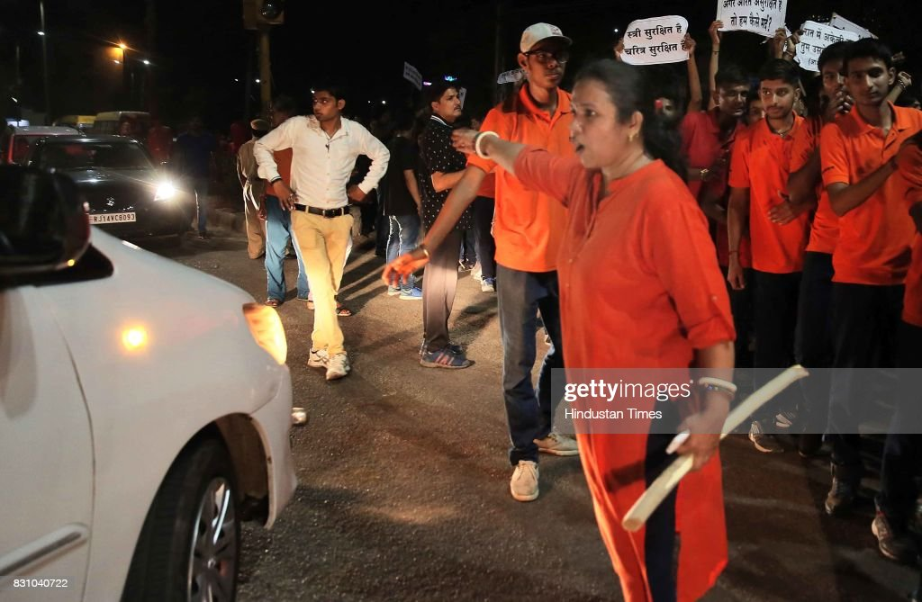 A teacher with baton manages the passerbys and onlookers during the `Meri Raat Meri Sadak` campaign in which thousands of girls and boys from...
