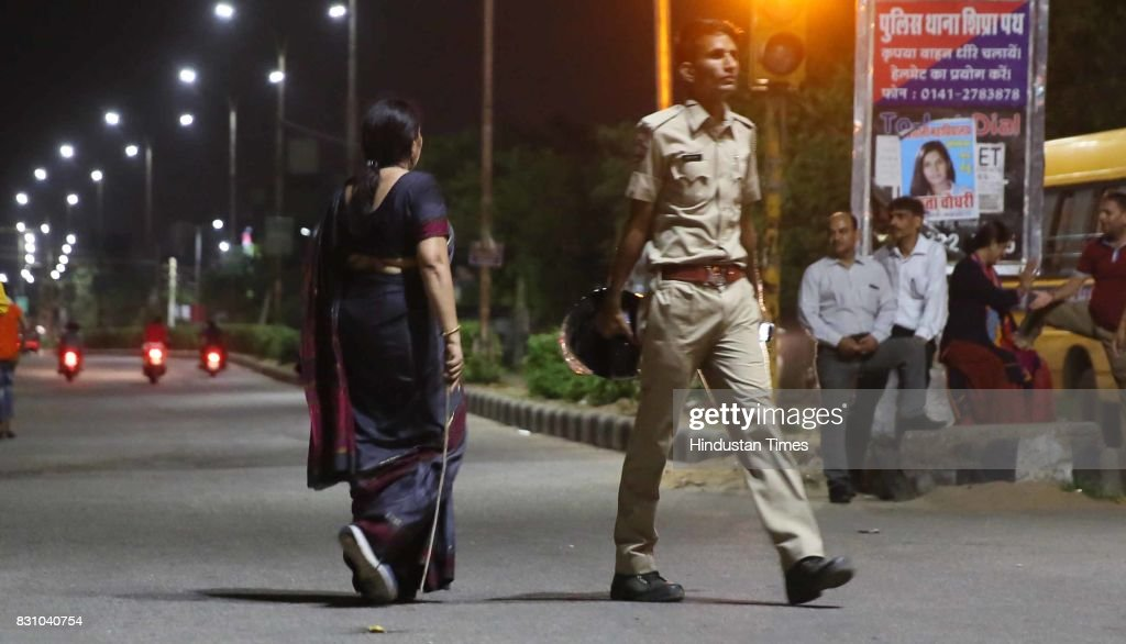 A teacher with baton manages the passerbys and onlookers during the 'Meri Raat Meri Sadak' campaign in which thousands of girls and boys from.