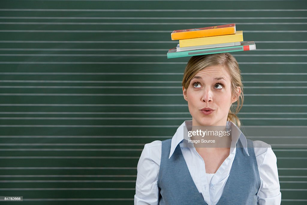 Teacher with books on her head : Stock Photo