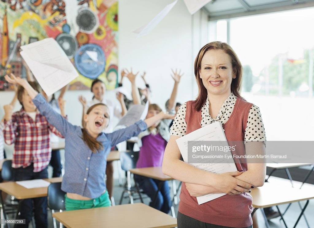 Teacher with celebrating students in classroom : Stock Photo
