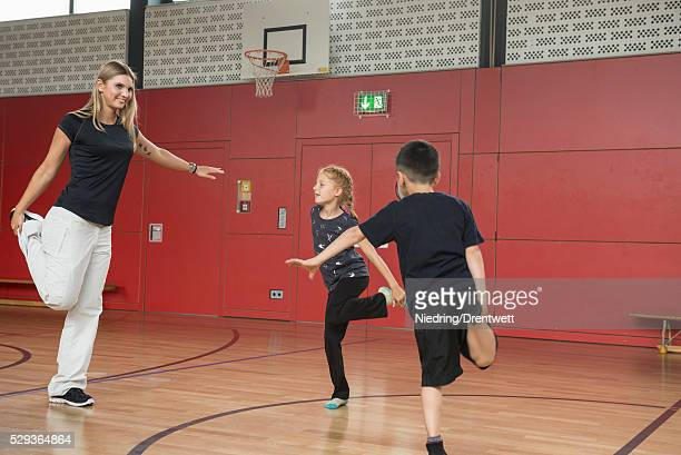 teacher with children doing exercise in sports hall, munich, bavaria, germany - kurdish girl stock photos and pictures