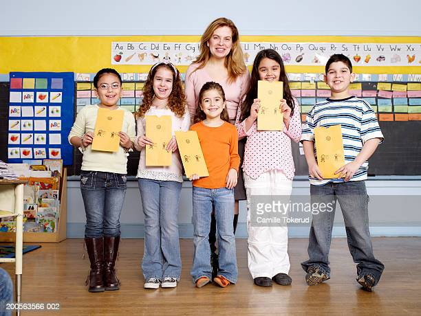 Teacher with children (6-9) holding report cards in classroom,portrait