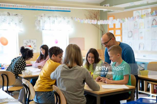 teacher with children in classroom - human age stock pictures, royalty-free photos & images