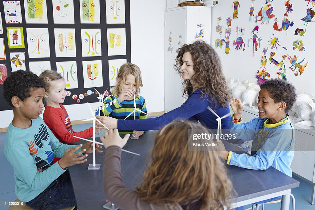 Teacher with children playing with wind turbines : Stock Photo