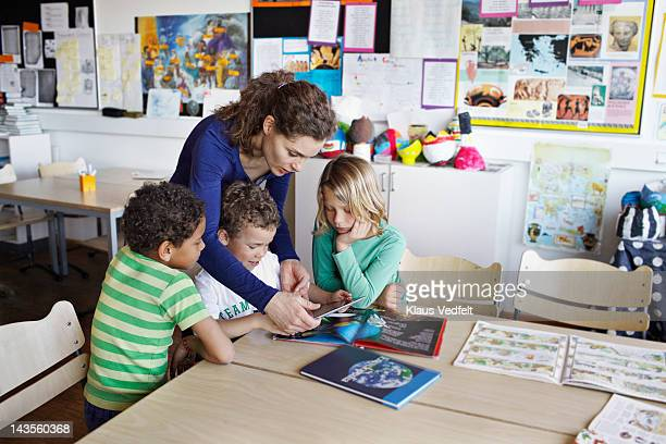 teacher with children using tablet - teacher bending over stock photos and pictures
