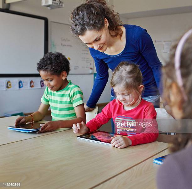 teacher with children using tablets - teacher bending over stock photos and pictures