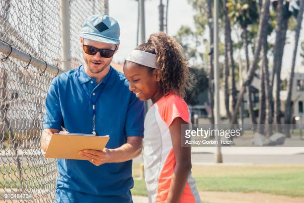 teacher with clipboard talking to teenage schoolgirl soccer player on school sports field - pe teacher stock photos and pictures