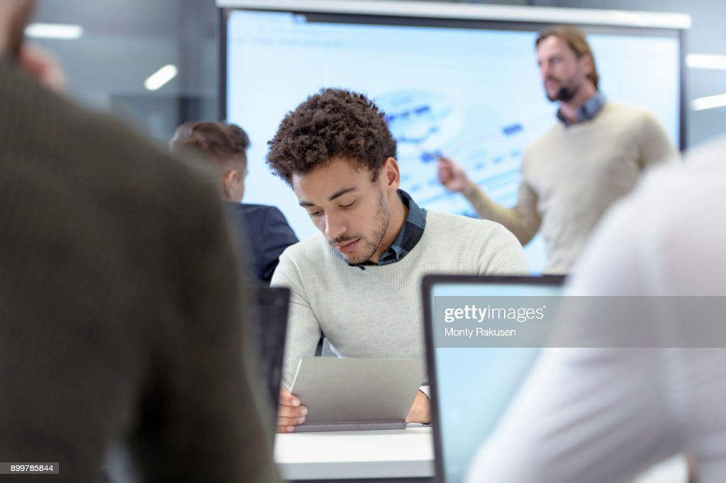 Teacher with engineering apprentices in classroom of railway engineering facility : Stock Photo