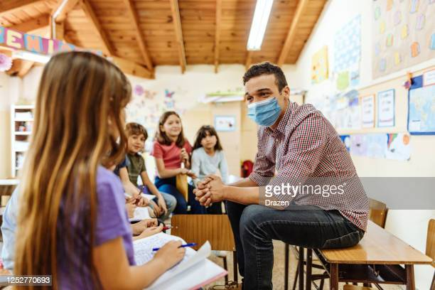 teacher with face mask motivating kids to be active in classroom after coronavirus - instructor stock pictures, royalty-free photos & images