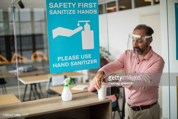 teacher with face shield disinfecting hands with hand sanitizer before entering classroom - reopening stock pictures, royalty-free photos & images
