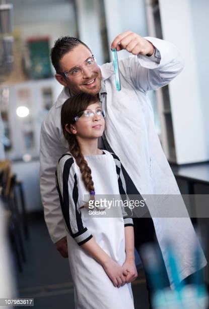 Teacher with girl in school laboratory