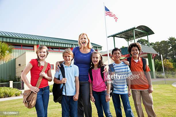 Teacher with  group of students outside school