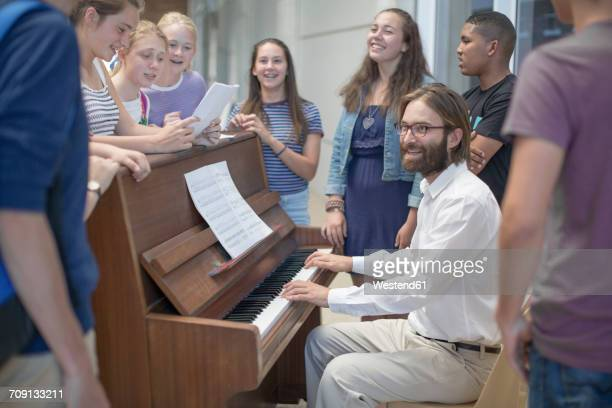Teacher with group of students standing around piano