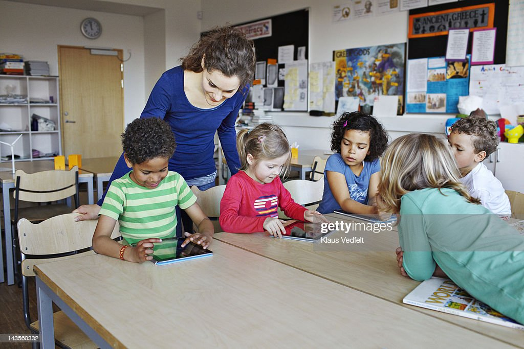 Teacher with kids using tablets : Stock Photo