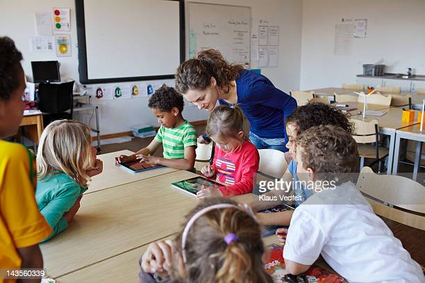 teacher with kids using tablets - teacher bending over stock photos and pictures
