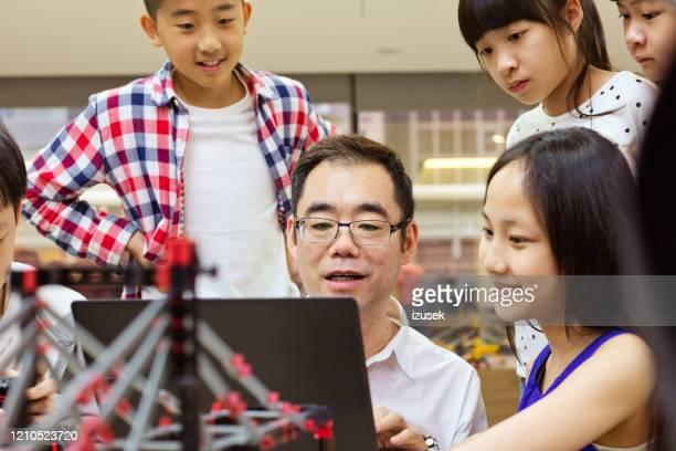teacher with laptop explaining robotics to students - izusek stock pictures, royalty-free photos & images