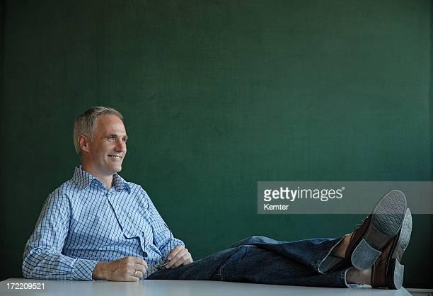 teacher with legs on desk