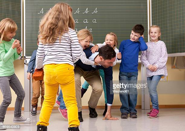 Teacher with playful pupils in classroom