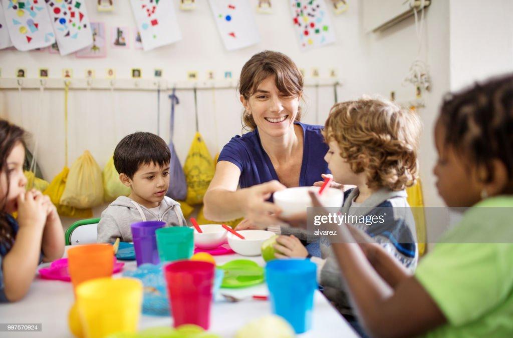 昼食時にデスクで就学前の子供と先生 : ストックフォト