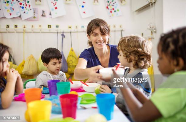 teacher with preschool kids at desk during lunch - preschool building stock pictures, royalty-free photos & images