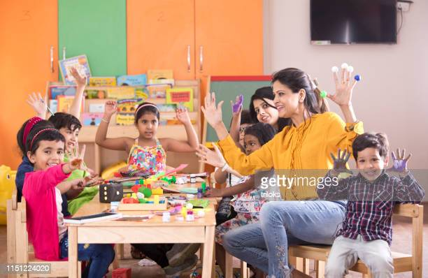 teacher with preschoolers finger painting at class - childhood stock pictures, royalty-free photos & images