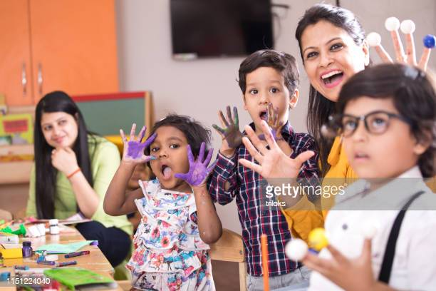 Teacher with preschoolers finger painting at class