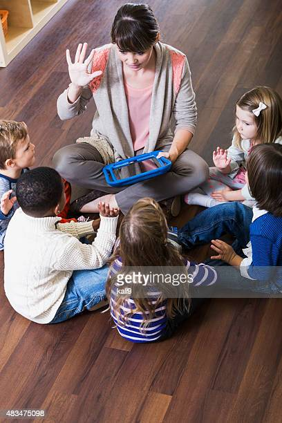 Teacher with preschoolers in class sitting on floor