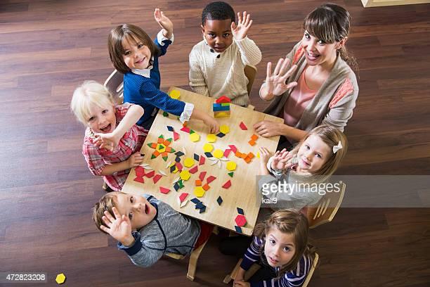 Profesor con preschoolers jugando con colorido formas