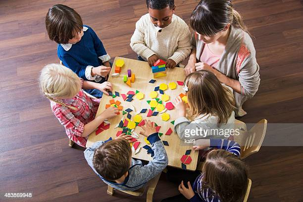 Teacher with preschoolers playing with colorful shapes