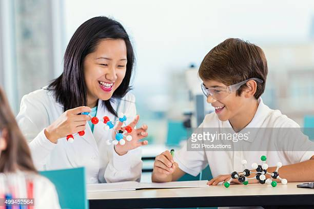 Teacher with preteen students teaching science class