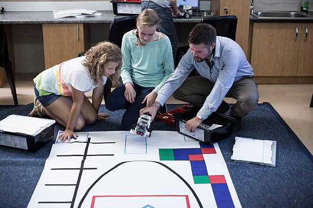 Teacher with schoolgirls on test track in robotics class