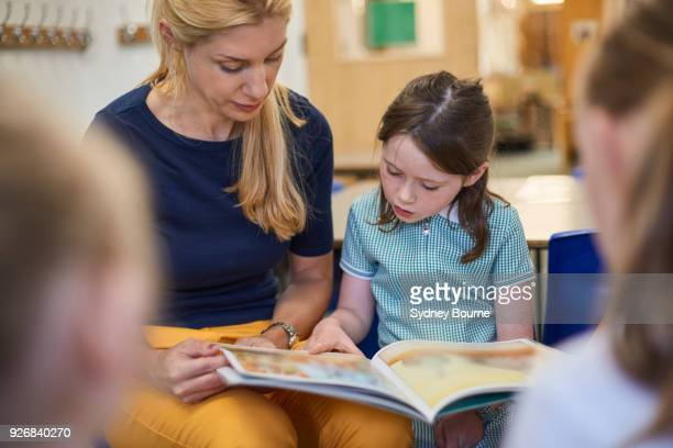 teacher with schoolgirls reading storybook in classroom at primary school - showing stock photos and pictures